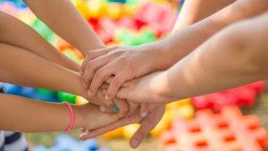 Manos unidas representando a una familia desarrollando una actividad común